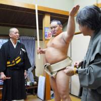 Who goes there?: Mongolian yokozuna Asashoryu poses as a model for a gatekeeper statue, to be carved out for Rengein Tanjoji Temple in Kumamoto Prefecture, during a photo session Thursday at a workshop in Kyoto, as priest Eisho Kawahara looks on. | KYODO PHOTO