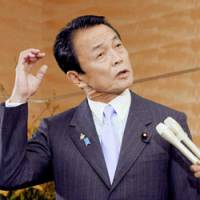 On the spot: Prime Minister Taro Aso fields questions from reporters on Dec. 26 at the Prime Minister's Official Residence. | KYODO PHOTO