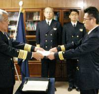 Sailing orders: Japan Coast Guard Commandant Teiji Iwasaki (left) hands Superintendent Third Grade Yukihiro Takeuchi a document Monday in Tokyo assigning eight officers to the antipiracy mission off Somalia. | KYODO PHOTO