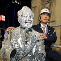 Pitchman: A construction worker shows off the statue of Colonel Sanders pulled from the Dotonbori River in central Osaka on Tuesday. | KYODO PHOTO