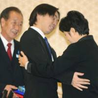 Poignant embrace: Koichiro Iizuka, the son of abductee Yaeko Taguchi, meets former North Korean agent Kim Hyon Hui on Wednesday in Busan, South Korea, as Taguchi's brother, Shigeo Iizuka, looks on. | KYODO PHOTO