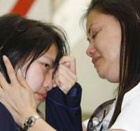 No words: Noriko Calderon wipes away tears as her mother, Sarah, tries to console her at Narita International Airport ahead of her parents' departure for the Philippines on Monday. | KYODO PHOTO