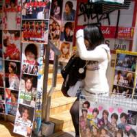 Marketing talent: A fan enters a shop plastered with photos of 'Johnnies' in the Harajuku district of Shibuya Ward, Tokyo, last week. | SATOKO KAWASAKI PHOTO