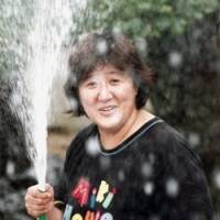 It's just water: Masumi Hayashi aims water toward a media crew in the garden of her Wakayama home in August 1998 before her arrest over the fatal curry poisonings in her neighborhood the previous month. | KYODO PHOTO