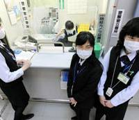 Precautionary move: Foreign-exchange clerks wear masks Monday at Kansai International Airport in Osaka Prefecture, as the nation's major airports gear up for a possible spread of swine flu. | KYODO PHOTO