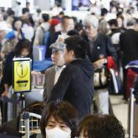 In the know: People wearing masks wait Tuesday in a departure lobby at Narita International Airport in Chiba Prefecture after the World Health Organization raised its flu pandemic alert level to Phase 4. | KYODO PHOTO