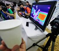 Illuminating: Photographers snap a thermal camera system that monitors body temperatures during a news conference at Yokohama Arena, where the World Table Tennis Championships are being held Friday. | AP PHOTO