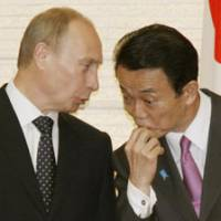 Eye to eye: Prime Minister Taro Aso and his Russian counterpart, Vladimir Putin, chat during a signing ceremony for a bilateral pact Tuesday night in Tokyo. | KYODO PHOTO