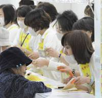 Lottery fever: Clerks in masks sell tickets for the Dream Jumbo lottery at an outlet in Kita Ward, Osaka, on Monday. The lottery's top prize is worth 200 million. | KYODO PHOTO
