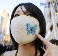 Fashionable protection: A woman wears a mask decorated with a butterfly Wednesday in Kobe, the focal point of the H1N1 swine flu outbreak. | KYODO PHOTO