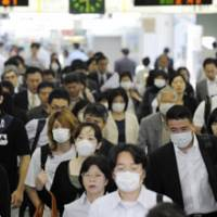 Playing it safe: Commuters wear masks as they make their way through JR Mizonokuchi Station in Kawasaki on Thursday. | KYODO PHOTO