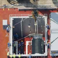 Easy does it: A container of mixed uranium-plutonium oxide (MOX) from France is lifted from the hold of the Pacific Heron on Saturday at a nuclear power plant in Genkai, Saga Prefecture. | KYODO PHOTO