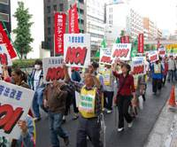 'Just say no': More than 200 protesters march through Tokyo's Shinbashi district Sunday with signs opposing revisions to the immigration law. | KAZUAKI NAGATA PHOTO