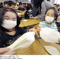 Real-world education: Elementary school students work with handmade masks Monday as classes resume at their school in Suita, Osaka Prefecture. | KYODO PHOTO