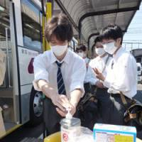 Taking no chances: Students of Kansai Okura Senior High School disinfect their hands before boarding a bus Monday morning as the school in Ibaraki, Osaka Prefecture, closed since mid-May due to swine flu, resumed classes. | KYODO PHOTOS