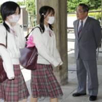 School of hard knocks: Kansai Okura Senior High School Principal Takaharu Miyanomae greets students as they return to classes Monday for the first time in two weeks.