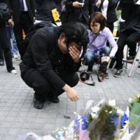 Painful memories: A man bursts into tears Monday at a crossing in Tokyo's Akihabara district where a killing rampage took place a year ago. | KYODO PHOTO
