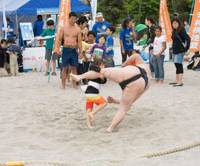 Sumo by the sea: A girl wearing a 'mawashi' (loincloth) throws a sumo wrestler at a beach sumo event in May in Tokyo's Odaiba waterfront area. | BEACH LIFE JAPAN