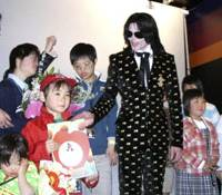 Better times: Michael Jackson smiles while posing for a photo with children from a Tokyo orphanage who were invited to an exculsive fan event in Tokyo on March 8, 2007. | AP PHOTO