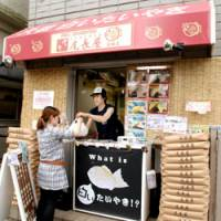 Pancake monger: An Onagaya 'taiyaki' stall in the Kamata district of Ota Ward, Tokyo, serves a customer Friday. | YOSHIAKI MIURA PHOTO
