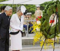 To the fallen: Emperor Akihito and Empress Michiko offer silent prayers Wednesday to the U.S war dead after they set a wreath on a stand at the National Memorial Cemetery of the Pacific in Hawaii. | KYODO PHOTO