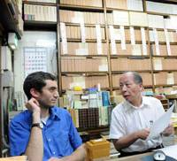 Old tomes: Isseido Booksellers President Takehiko Sakai talks to intern Peter Bernard at the antiquarian bookstore in Jinbocho in Chiyoda Ward, Tokyo. | SATOKO KAWSAKI PHOTO