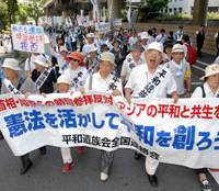 Give peace a chance: Relatives of the war dead who oppose politicians' visits to Yasukuni Shrine march near the controversial site in Chiyoda Ward, Tokyo, on Saturday with a banner calling for peace based on the Constitution. | YOSHIAKI MIURA PHOTO
