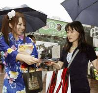 Working the crowd: A student wearing a 'yukata' summer kimono distributes fliers Aug. 2 in front of JR Shibuya Station in Tokyo calling on people to vote in the upcoming Lower House election. | KYODO PHOTO