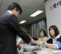 Absentee ballot: A Japanese voter receives a ballot Wednesday at a polling station set up at the Japanese Embassy in Beijing as early voting by absentees overseas for the Aug. 30 election begins. | KYODO PHOTO