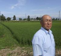 Rural link: Rice farmer Chikara Inoue, 64, stands by a paddy in Aomori on Aug. 6, while Democratic Party of Japan candidate Hokuto Yokoyama speaks at his office in the city the same day. | AP PHOTO