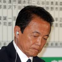 Staggered: Prime Minister Taro Aso faces the media Sunday evening at Liberal Democratic Party headquarters in Tokyo as reports came in of the ruling party's crushing defeat. | YOSHIAKI MIURA PHOTO