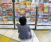 Spoiled for choice: A woman checks out brochures outside a travel agency in Tokyo on Sept. 6 ahead of the five-day 'silver week' holiday period that begins Sept. 19. | BLOOMBERG
