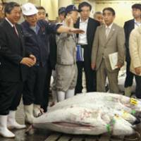 Making the rounds: Farm minister Hirotaka Akamatsu (left) listens to an official at the Tsukiji fish market in Tokyo on Thursday. | KYODO PHOTO