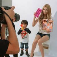 For fashion-conscious moms: A 25-year-old mother holds a booklet recommending homemade baby food during a photo shoot with her son for the monthly magazine I LOVE mama. | KYODO PHOTO