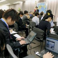 Broader access: Employees of Internet media sites broadcast a news conference live by Foreign Minister Katsuya Okada on Sept. 29. In the past, only press club members were allowed to attend briefings at the ministry. | KYODO PHOTO