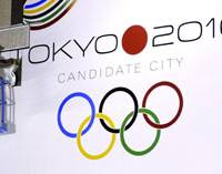A sign of the times: A worker removes a huge poster pitching Tokyo's failed bid to host the 2016 Olympic Games at the Tokyo Metropolitan Government building in Shinjuku Ward early Sunday. | KYODO PHOTO