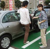 Signal your intent: An instructor escorts her student to a vehicle at the Musashi-Sakai Driving School in Musashino, western Tokyo, in August. | KYODO PHOTO