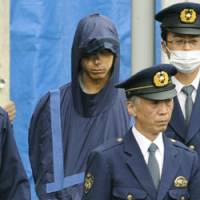 Next stop: Tatsuya Ichihashi, the suspect in the 2007 slaying of Lindsay Ann Hawker, is escorted by police Thursday as he leaves Gyotoku Police Station in Chiba Prefecture bound for the Chiba District Public Prosecutor's Office. | KYODO PHOTO