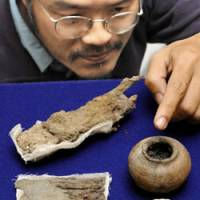 Rare find: Masahiro Ikeda, curator at the Hyogo Prefectural Museum of Archaeology, points Wednesday to a pot from an ancient makeup kit discovered in a tomb in Nishiwaki, Hyogo Prefecture. Above left is a rusty clod in which a pair of iron scissors and tweezers are embedded. Also in the picture is a Chinese bronze mirror. | KYODO PHOTO