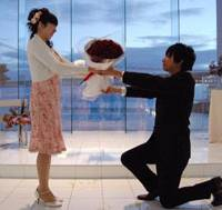 Tying the knot: Naoya Sakamoto gets down on one knee to present his girlfriend, Madoka Miyake, with a bouquet of red roses during a professionally choreographed marriage proposal in Kobe on May 29. | KYODO PHOTO