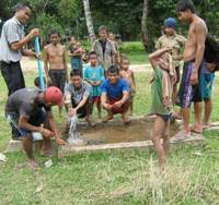 Fountain of life: Laotians repair a well in the village of Nakhanon in August. | JAPAN INTERNATIONAL VOLUNTEER CENTER