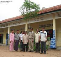 School is in: Teachers pose in front of their school with the leader of Beoung Kak village in Cambodia. The school was renovated by Amatak in August. | COURTESY OF AMATAK