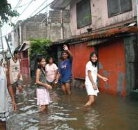 Storm-tossed lives: Residents of Muntinlupa, Philippines, wade through floodwater after Typhoon Ketsana devastated the area in September. | COURTESY OF PAG-ASA GROUP JAPAN