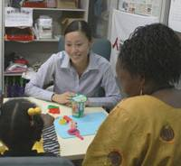 Looking for a way out: A mother and child from east Africa who are seeking asylum in Japan receive counseling from a member of the Japan Association for Refugees in June. The two lost their government support earlier in the year, leaving them little money to buy essential goods. | COURTESY OF JAPAN ASSOCIATION FOR REFUGEES