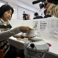 Hot or not: Hiroko Aki, a resident of Nagareyama, Chiba Prefecture, places a food sample in a radiation detector Oct. 11 at Bec-Miru, a DIY irradiation scanning store in nearby Kashiwa. | YOSHIAKI MIURA PHOTO