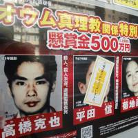 Two to go: A wanted poster Monday bears a sticker reading 'Thank you for your cooperation' over a mug shot of Makoto Hirata, who was arrested after turning himself in on New Year's eve. | KYODO PHOTO
