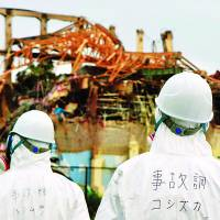 Where to start?: Members of an investigative government panel view the crippled Fukushima No. 1 plant in June. | KYODO PHOTO