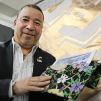 In style: Kimono designer Nobuaki Tomita shows off a case for an iPad tablet computer made of fabric for sashes recently in Kyoto. | KYODO