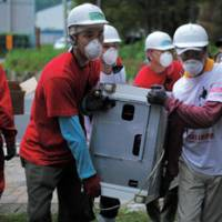 Lifting spirits: Members of volunteer group Team Heal Japan remove debris from a home in Iwaki, Fukushima Prefecture, in July. | COURTESY OF TEAM HEAL JAPAN