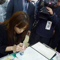 Special delivery: An Okinawa prefectural employee stamps a key report on the Futenma base relocation Thursday. | KYODO PHOTO